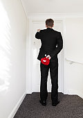 Man knocking on door holding heart shaped box