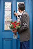 Man knocking on door with bouquet