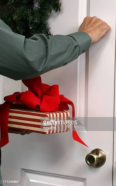 Man Knocking on door with gift in hand.