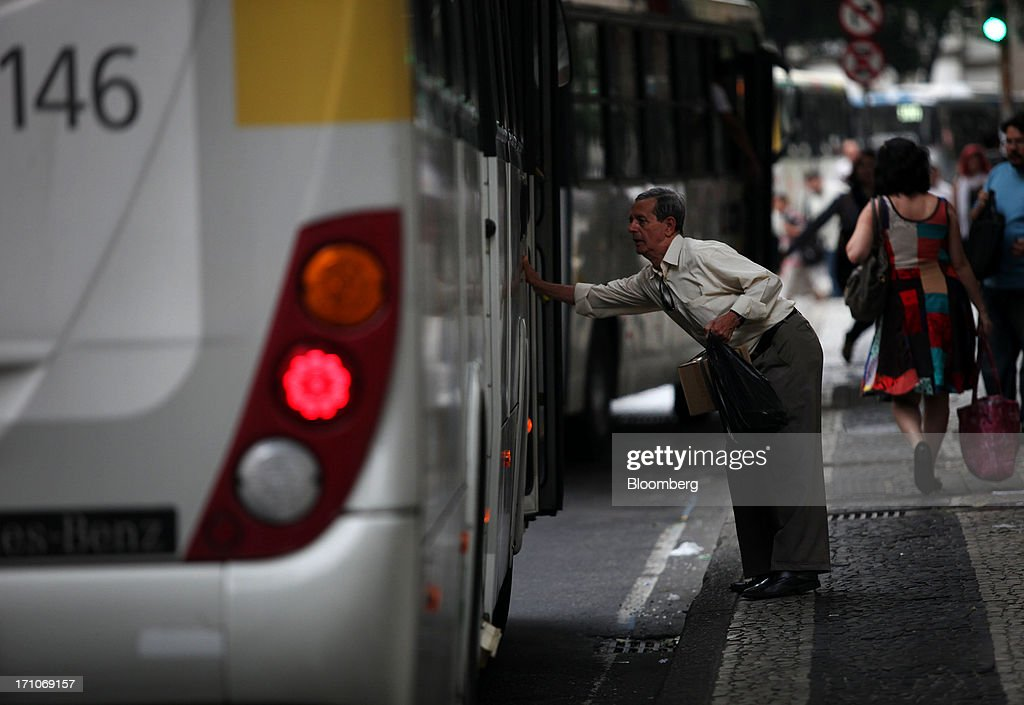 A man knocks the door of a bus as it leaves the station on Presidente Getulio Vargas Avenue in Rio de Janeiro, Brazil, on Friday, June 21, 2013. Brazils swelling street rebellion claimed its second fatality in the largest and most violent protests yet, as 1 million demonstrators rallied for better public services and an end to corruption. Photographer: Dado Galdieri/Bloomberg via Getty Images