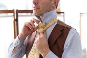 Man knotting his necktie while dressing in a formal shirt and waistcoat in a close up view of his hands