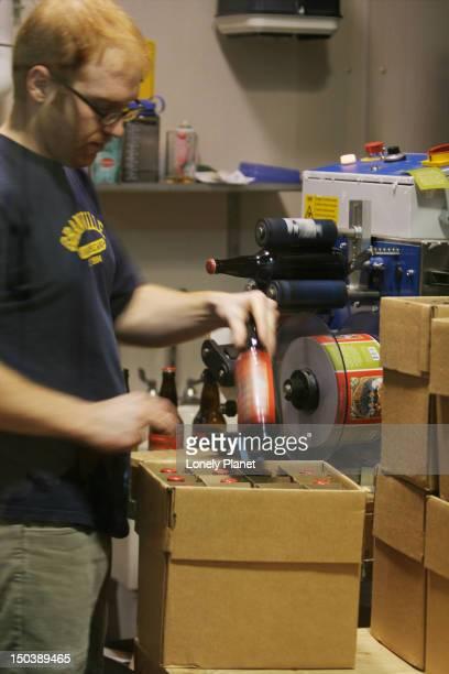 Man labelling bottles at Granville Island Brewing.
