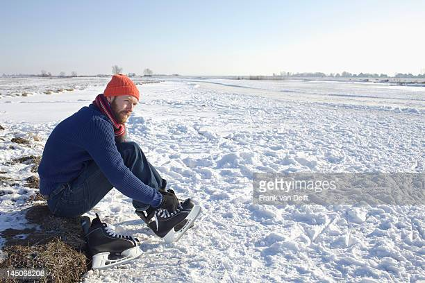 Man lacing up ice skates in snowy field