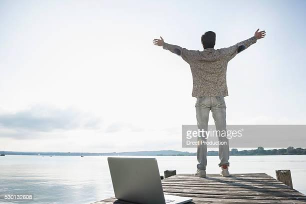 Man lake happy laptop computer jetty