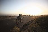 Man landboarding on road at sunset