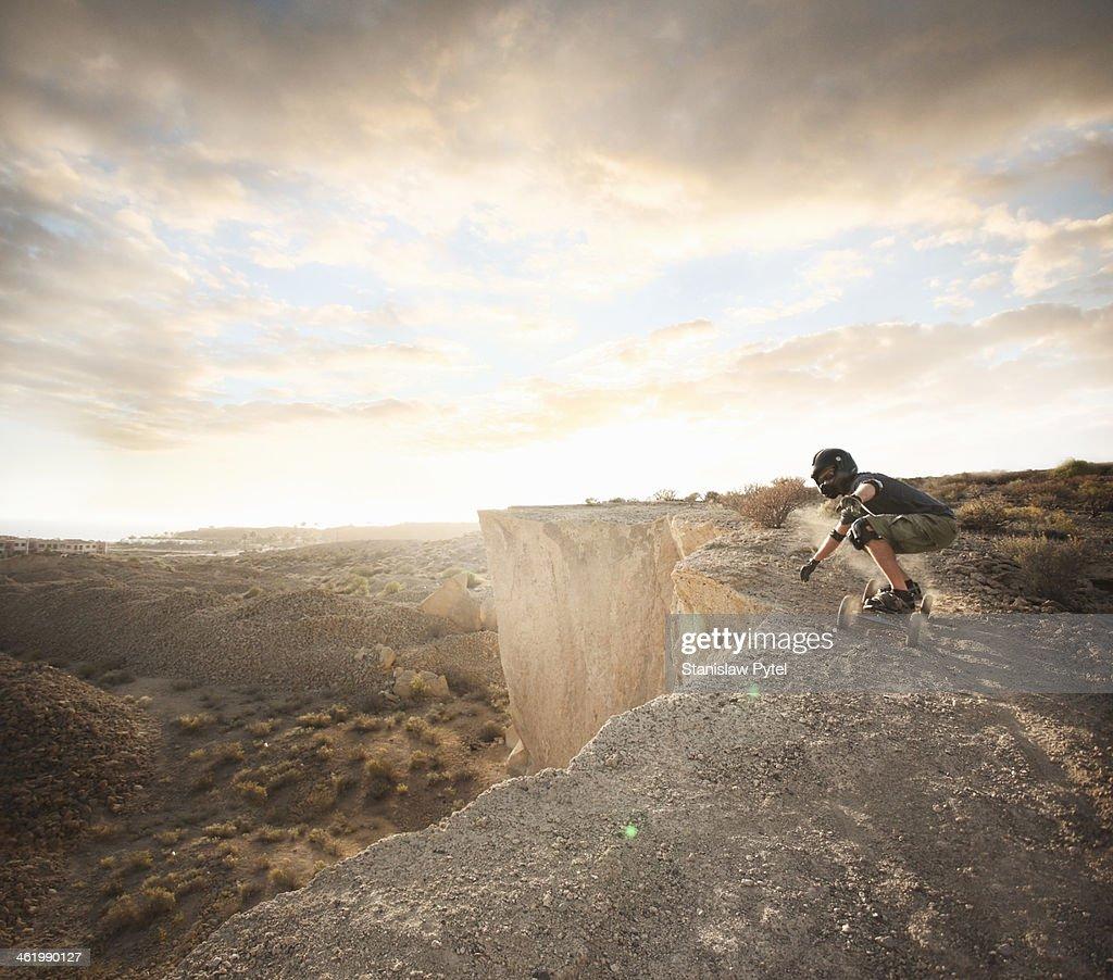 Man landboarding on rocks
