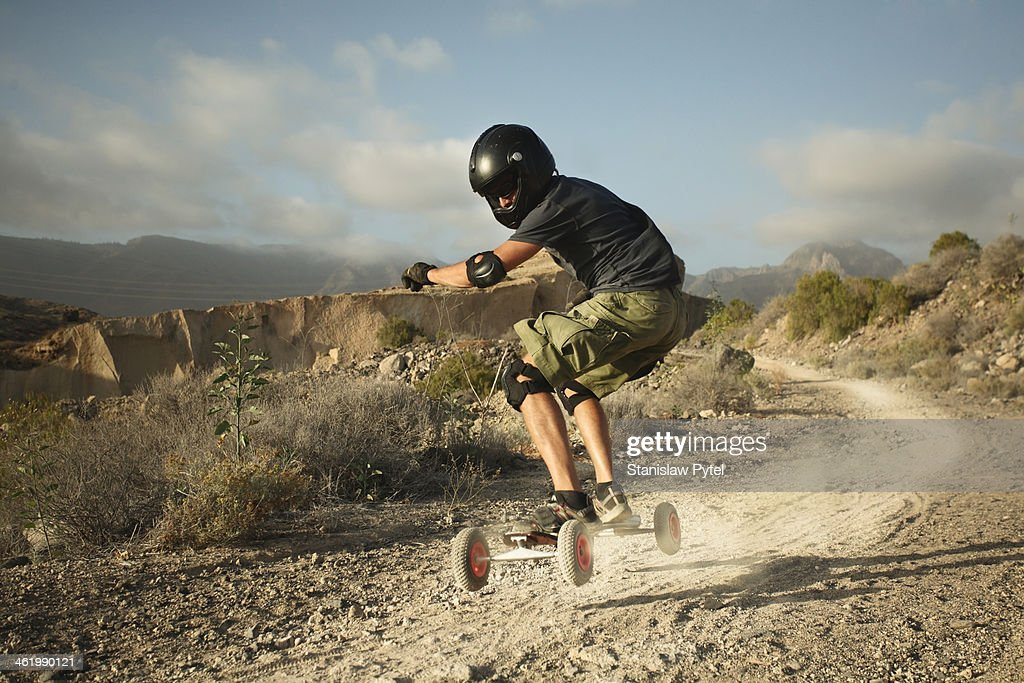 Man landboarding on rocky road
