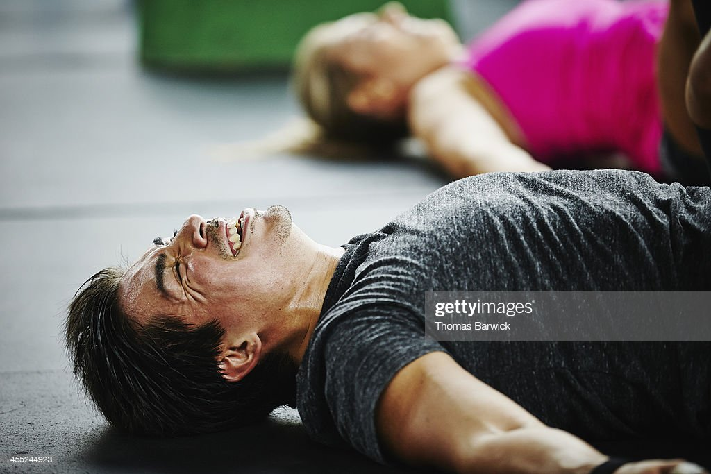 Man laughing and grimacing lying on floor of gym : Stock Photo
