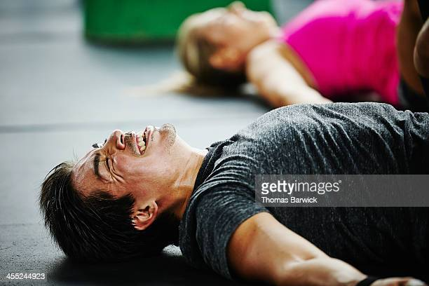 Man laughing and grimacing lying on floor of gym