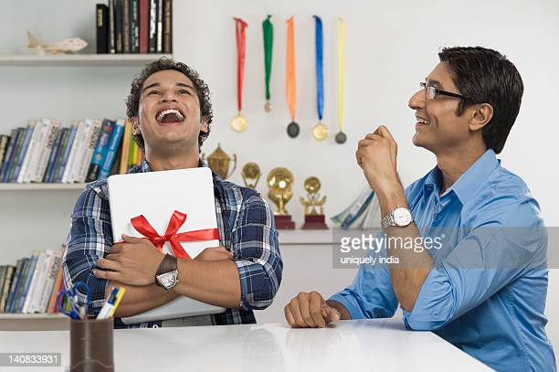 Man laughing and hugging a laptop gifted by his father