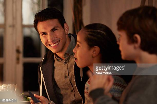 Man laughing at dinner in garden house