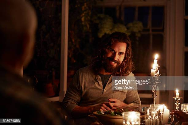 Man laughing at dinner in greenhouse