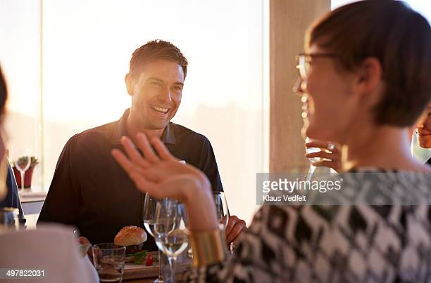 Man laughing in conversation with friends