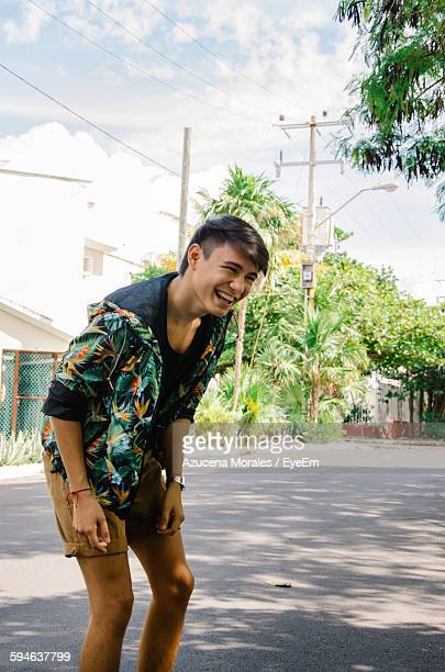Man Laughing While Walking On Road Against Sky