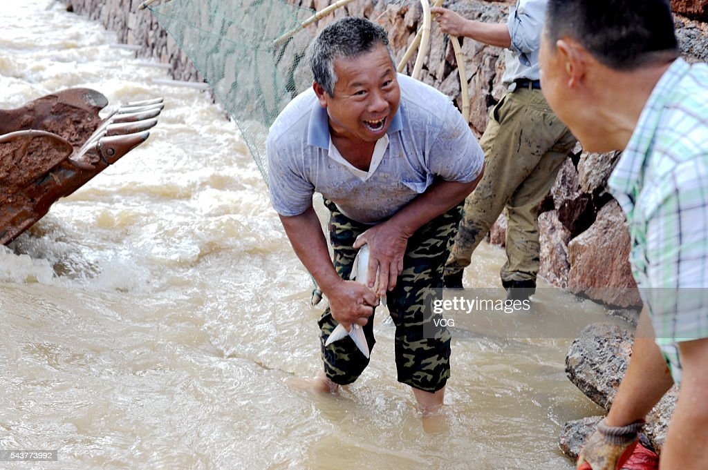 A man laughs while holding a fish caught at Huhaitang basin after heavy rain on June 30, 2016 in Jinhua, Zhejiang Province of China. Heavy rain hit southeast China's Jinhua City, bringing a number of fish from upstream and local citizens and nearby workers working on China National Highway 330 (G330) rushed to arrest fish in a basin.