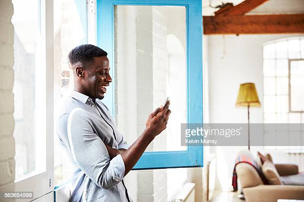 A man laughs while using his smartphone