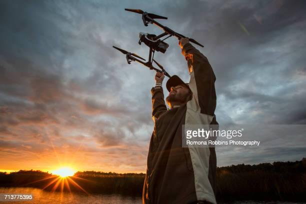 Man launching drone at sunrise, Homosassa, Florida, USA