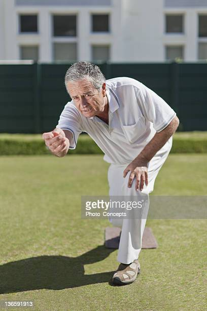 Man lawn bowling on grass