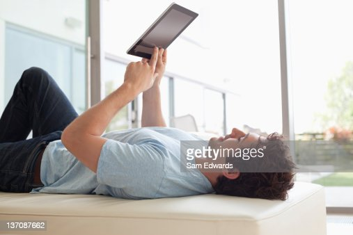 Man laying down using digital tablet : Stock Photo