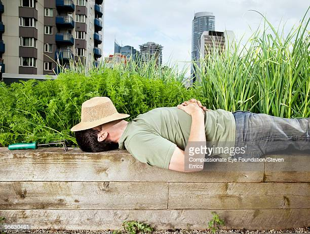 man laying down with hat over his face