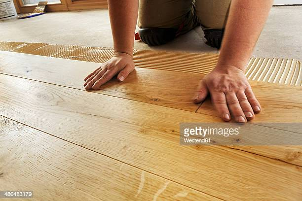 Man laying finished oak parquet flooring, close-up