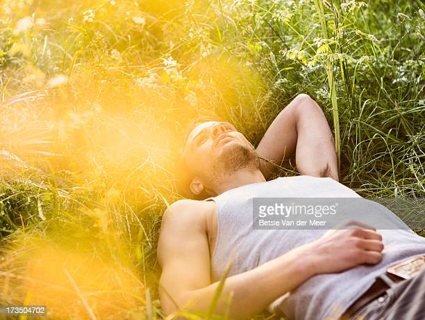 Man laying in grass,daydreaming.