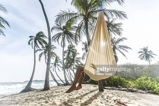 Man laying in hammock on a tropical beach.
