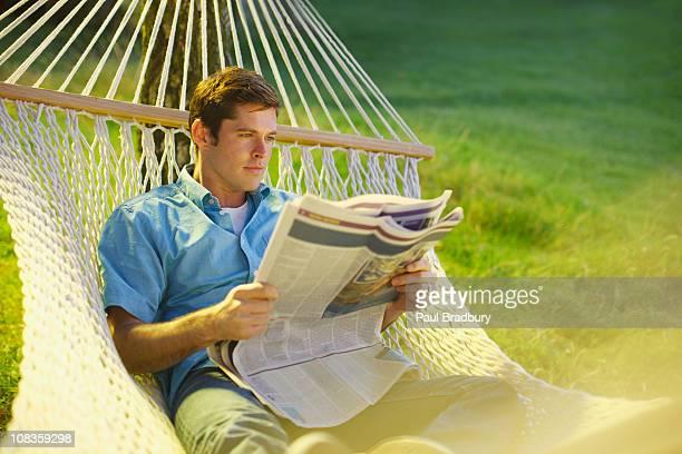 Mann in einer Hängematte lesen Zeitung verbringen