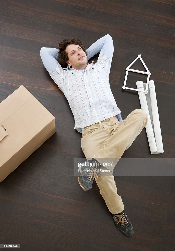 Man laying on floor with boxes : Stock Photo