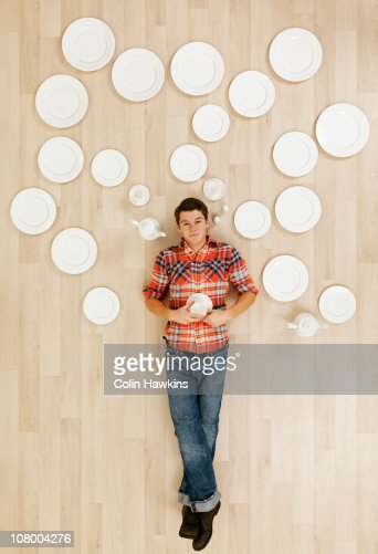 man laying on floor with crockery thought bubbles : Stock Photo