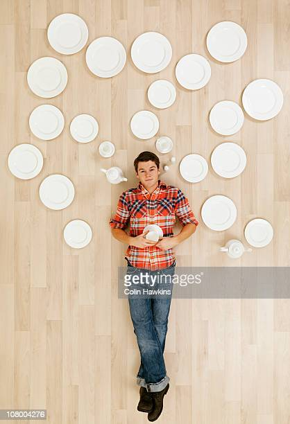 man laying on floor with crockery thought bubbles