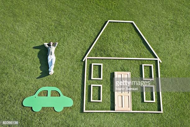 Man 花輪を芝生の隣にあり、お車のアウトライン