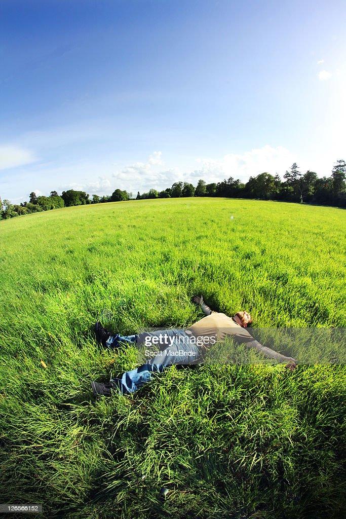 Man laying on grass : Stock Photo