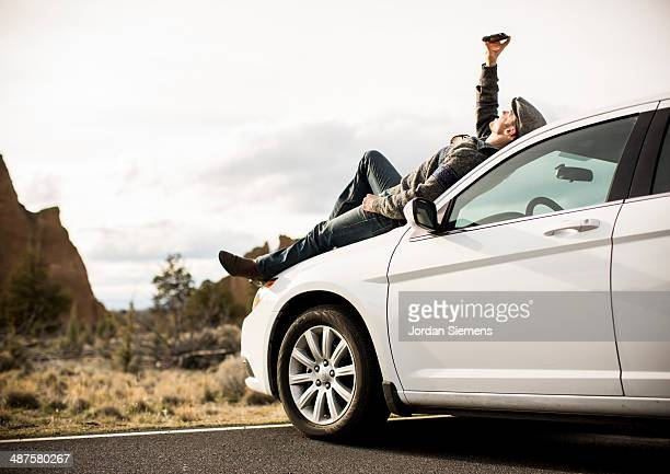 Man laying on his car using his cell phone.