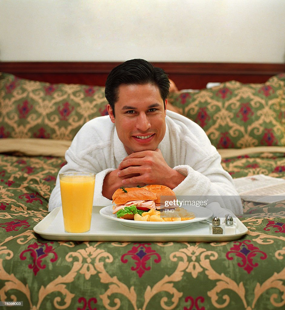 Man laying on hotel bed with tray of food : Stock Photo