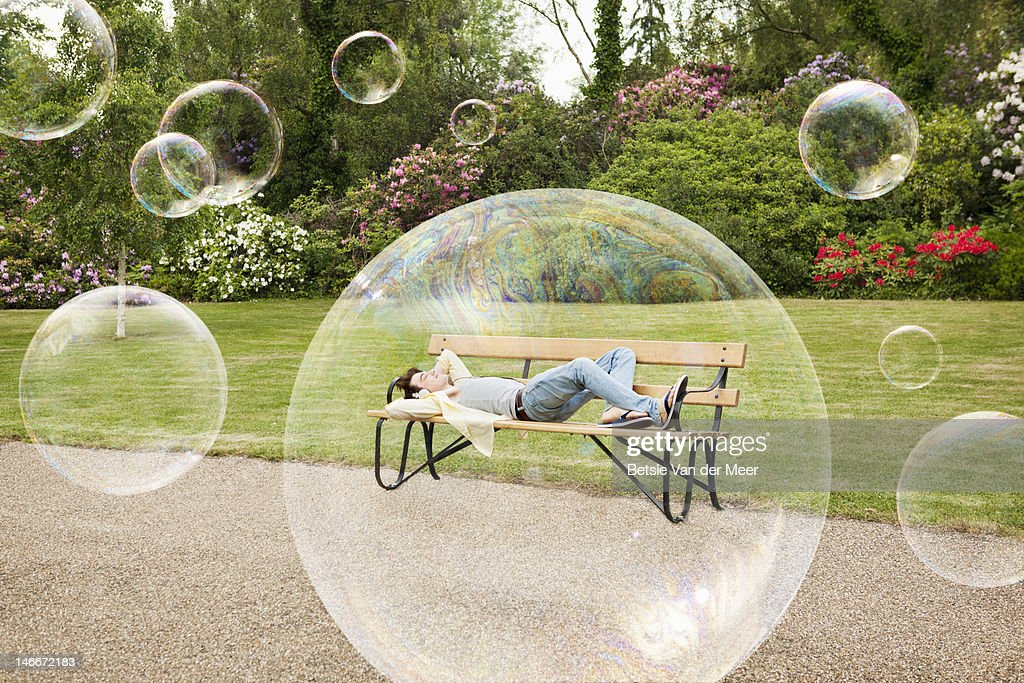man laying on park bench, surrounded by bubbles. : Stock Photo