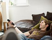 Man laying on sofa watching television