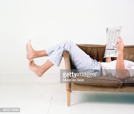 Man laying on sofa with newspaper