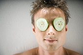 Man laying on spa table with cucumber slices on eyes