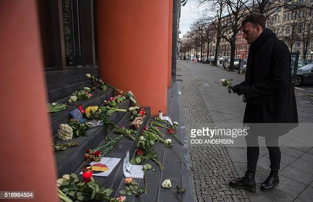 A man lays a flower outside the Belgian embassy in Berlin on March 22 2016 Security was tightened across Europe and transport links paralysed after a...