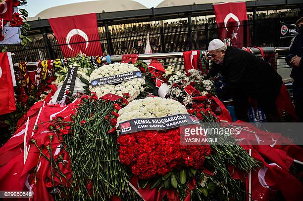 TOPSHOT A man lays a flowers at the scene of December 10 blasts outside the Vodafone Arena football stadium on December 14 2016 in Istanbul The death...