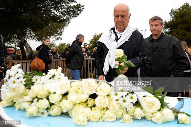 A man lays a rose at the end of a march in homage to the three men killed by an apparently deranged teenager on April 27 2013 in the southern French...