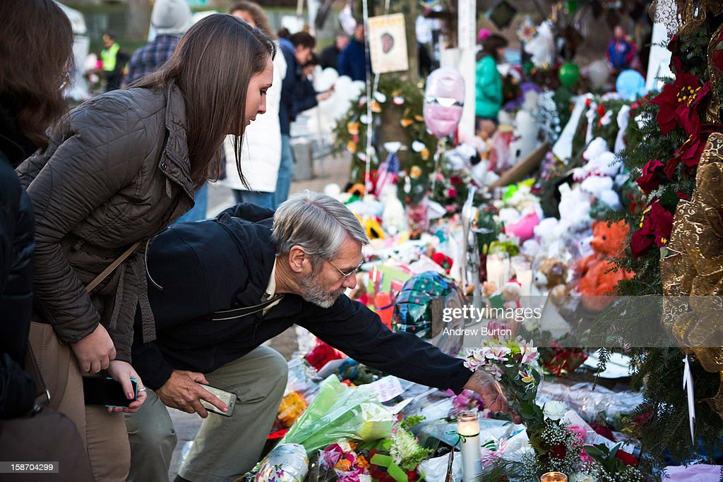 A man lays flowers at a memorial for those killed in the school shooting at Sandy Hook Elementary School on December 24, 2012 in Newtown, Connecticut. Donations and letters are pouring in from across the country as the town tries to recover from the massacre.