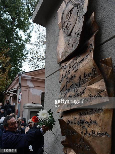 A man lays flowers at a plaque commemorating slain antiKremlin reporter Anna Politkovskaya in Moscow on October 7 shortly after it was unveiled at...