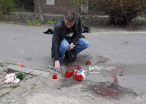 A man lays flowers at the murder scene proRussian journalist Oles Buzyna after he was shot dead in KievUkraine on April 16 2015 Buzyna was shot dead...