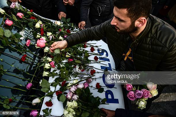TOPSHOT A man lays flowers on a police vehicle as people pay their respects outside the Vodafone Arena football stadium in Istanbul on December 11 a...