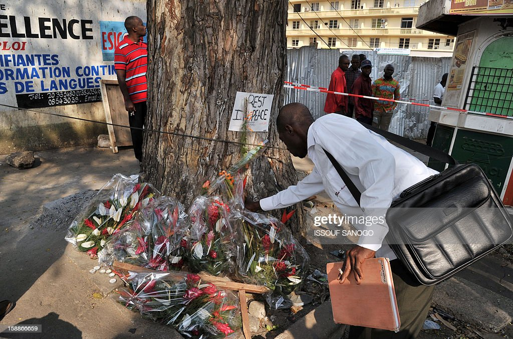 A man lays flowers on January 2, 2013 at a tree in the street of Abidjian where at least 60 persons died in a stampede among crowds gathered for celebratory New Year's Eve fireworks that also left dozens injured. Ivory Coast began today three days of national mourning.