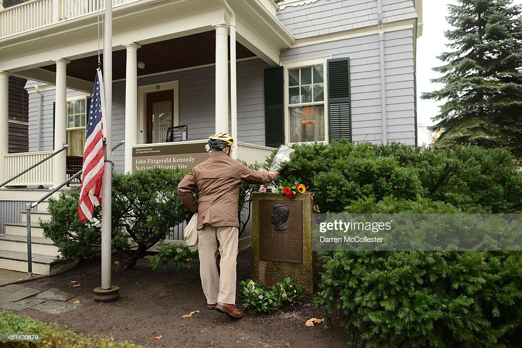 A man lays flowers on the marker at the birth home of John F. Kennedy at 83 Beals Street November 22, 2013 in Brookline, Massachusetts. Kennedy, born in Brookline Massachusetts, was killed 50 years ago on this day by Lee Harvey Oswald in Dallas Texas in 1963.