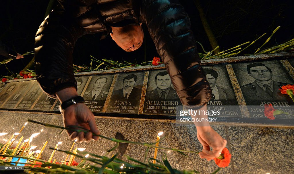 A man lays flowers to portraits at the monument to Chernobyl victims in Slavutich, some 50 kilometres (30 miles) from the accident site, and where many of the power station's personnel used to live, during a memorial ceremony early on April 26, 2013. Ukraine on April 26 marks the 27th anniversary of the Chernobyl disaster which was the world's worst nuclear accident.