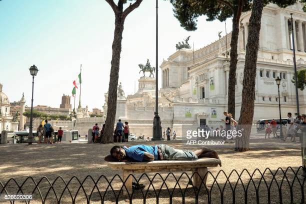 A man lays on a bench in the shadow under trees in front the 'Altare della Patria' in central Rome on August 5 as temperatures reached more than 40...